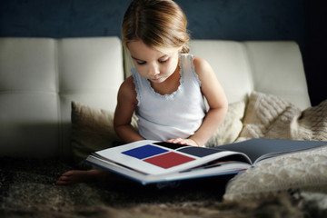 Girl looking at book while sitting on bed