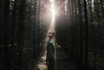Woman looking up while standing in forest