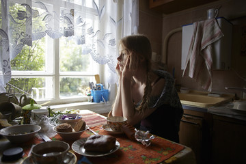 Thoughtful woman with hands on chin looking away while sitting by table at home