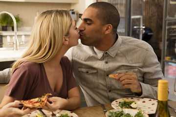 Young couple kissing at dining table