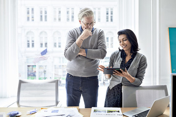 Businesswoman showing tablet computer to senior businessman while standing against window in creative office