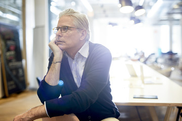 Thoughtful senior businessman looking away while sitting in brightly lit office