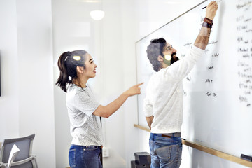 Business people discussing on whiteboard in office