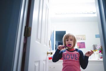 Portrait of girl brushing teeth while standing in bathroom