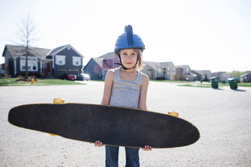 Portrait of girl in helmet carrying skateboard while standing on street during summer