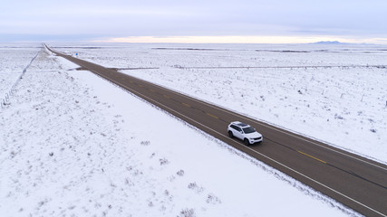 High angle view of vehicle moving on road amidst snow covered landscape against sky