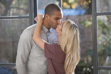 Couple kissing by window