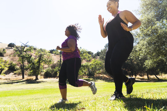 Low angle view of female friends jogging while exercising at park