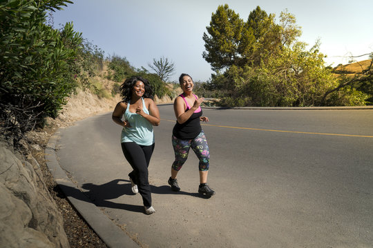 Happy female friends jogging on road during sunny day