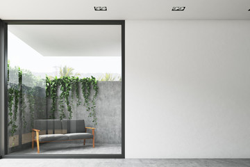 Gray sofa in a yard, plant on a wall