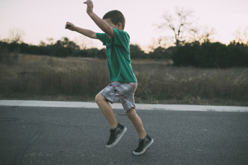 Side view of playful boy running on country road