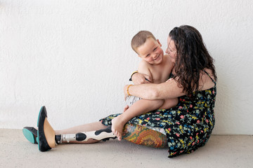Smiling mother with prosthetic leg embracing son at home