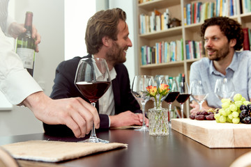 Cropped hands of bartender holding wineglass while friends talking at table in tasting room
