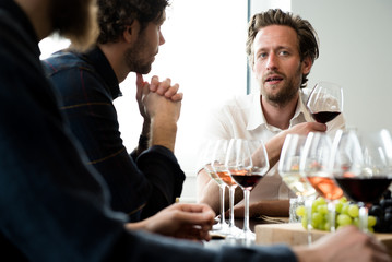 Friends talking while having wine in tasting room
