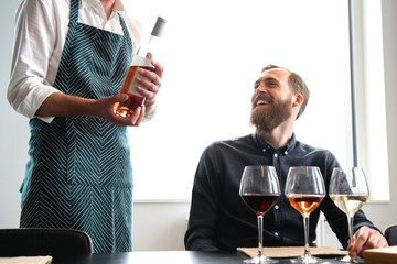 Midsection of bartender standing by laughing customer in tasting room