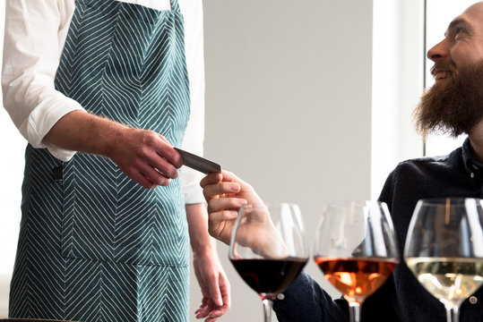 Customer making card payment to bartender in tasting room