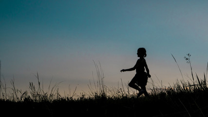 Silhouette girl walking on grassy field against clear sky during dusk