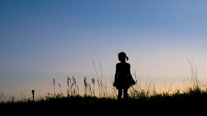 Silhouette girl standing on grassy field against clear sky during dusk