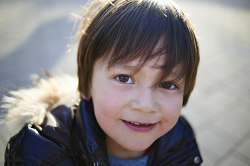 High angle portrait of confident boy standing on footpath