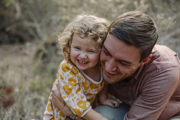 Smiling father embracing daughter while sitting outdoors