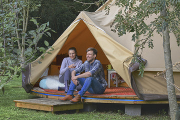Young couple drinking wine in tent.