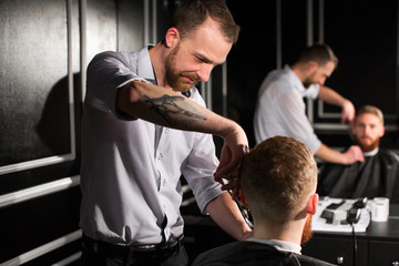 Master cuts hair and beard in the Barber shop. Hairdresser makes hairstyle using scissors and a metal comb.