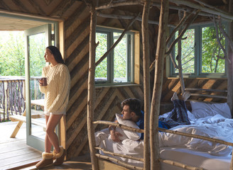 Young couple in log cabin bedroom.