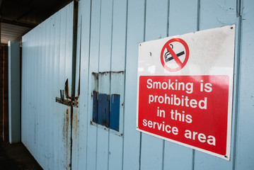 Sign on a gate warning that smoking is prohibited in this service area.