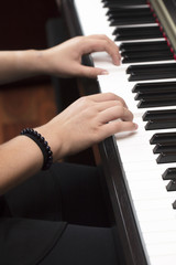 Young person playing the piano with both hands
