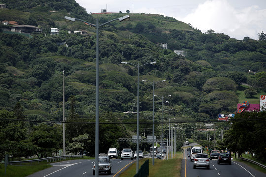Electric light poles are seen along a freeway in Santa Ana, Costa Rica