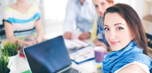 Portrait of attractive female  designer sittin on desk  in office