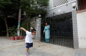 Rehana Khursheed Hashmi, 75, migrated from India with her family in 1960 and whose relatives, live in India, stands at the entrance of her house as her five year-old grandson Faraz Hashmi playing in Karachi,