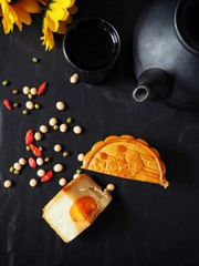 Festival moon cake with hot tea on black background