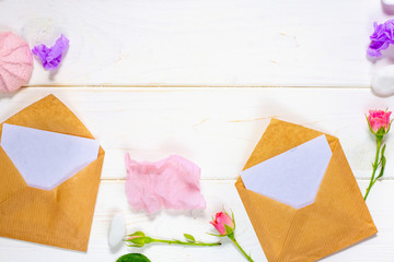 Envelope, paper blank and pink rose flower on white table top view in flat lay style for greeting card on Womans day.