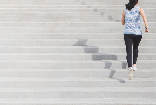 Young Asian sport woman running upstairs on the step with copy space. Concept of healthy lifestyle fitness sports.