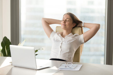 Calm smiling businesswoman relaxing at comfortable office chair hands behind head, happy woman resting in office satisfied after work done, enjoying break with eyes closed, peace of mind, no stress