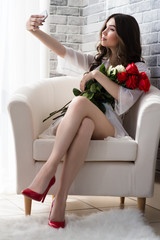 beautiful woman with bouquet roses makes selfie