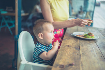 Mother and baby eating in a cafe by window