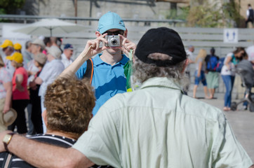 A young man taking a snapshot of his elderly parents on a tourist site. Indistinctive tourists on the background.