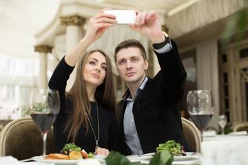 Beautiful couple taking selfie photo in a restaurant