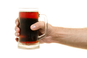A glass of kvass in a male hand