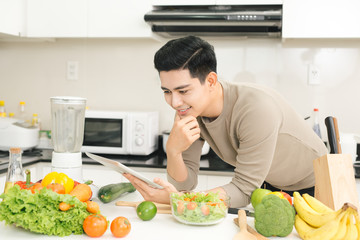 Asian handsome man looking recipe on laptop in kitchen at home