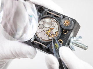 watchmaker in magnifier repairs wristwatch