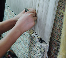 weaving and manufacturing of handmade carpets closeup. women's hands weave a carpet