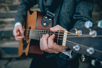Man's hands playing acoustic guitar. Background