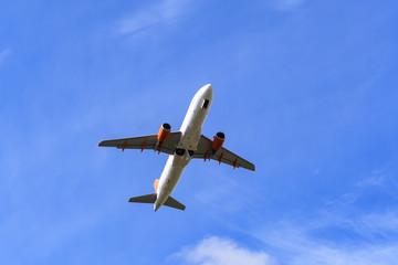 Flugzeug vor blauem Himmel fährt nach dem Start das Fahrwerk ein