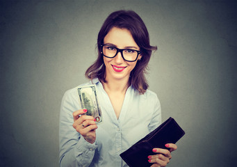 Successful young woman paying for herself holding wallet offering cash