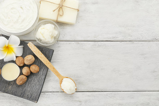 Different cosmetic products with shea butter on wooden table