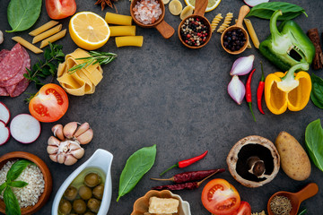 Italian food cooking ingredients basil, parmesan cheese ,garlic, olive oil , pine nut ,peppercorn and himalayan salt on dark stone background  flat lay and copy space.