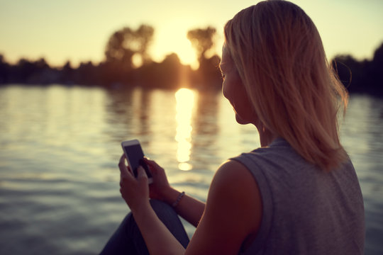 Woman near water with cellphone
